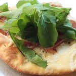 Pizza with prosciutto, fontina and arugula.